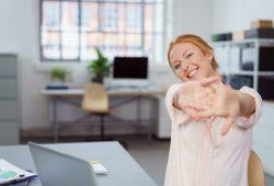 lachende frau im büro streckt die arme nach vorne